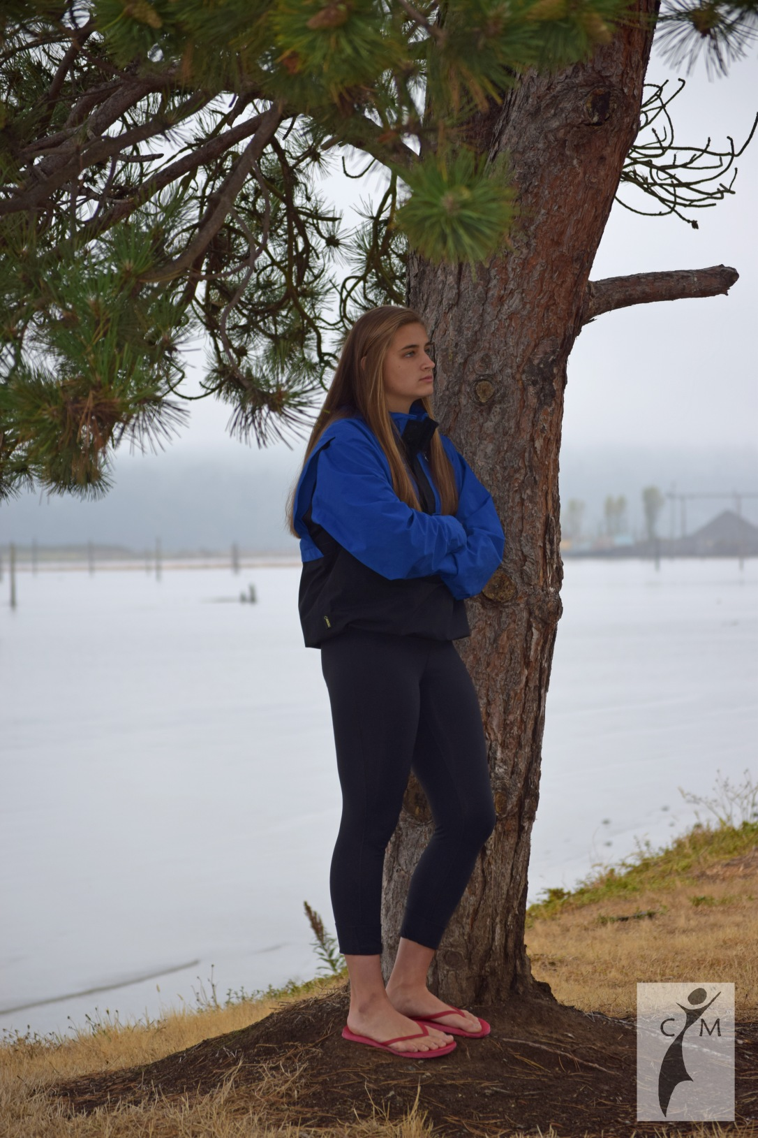 Young woman by tree on shore