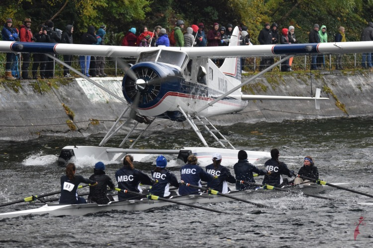Rowers on the Montlake Cut passing a seaplane